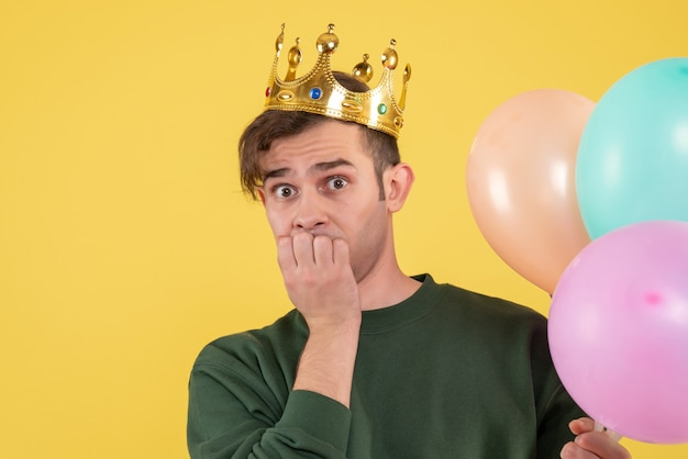Vooraanzicht verwarde jonge man met kroon houden ballonnen op geel