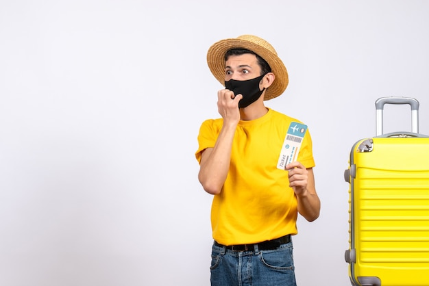 Vooraanzicht verwarde jonge man met strohoed staande in de buurt van gele koffer met reisticket