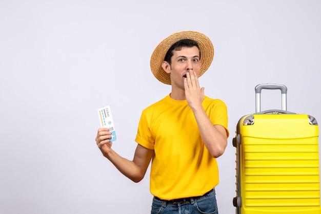 Vooraanzicht verwarde jonge toerist die zich dichtbij het gele reiskaartje van de kofferholding bevindt