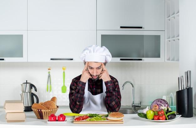 Vooraanzicht verwarde mannelijke chef-kok die aan iets in de keuken denkt