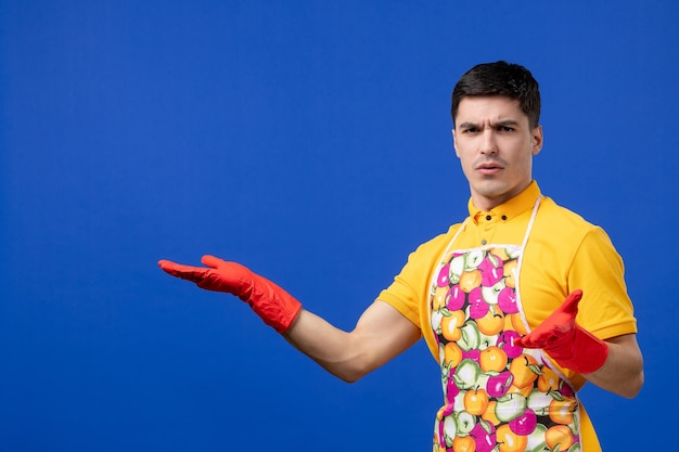 Vooraanzicht verwarde mannelijke huishoudster in schort wijzend op iets