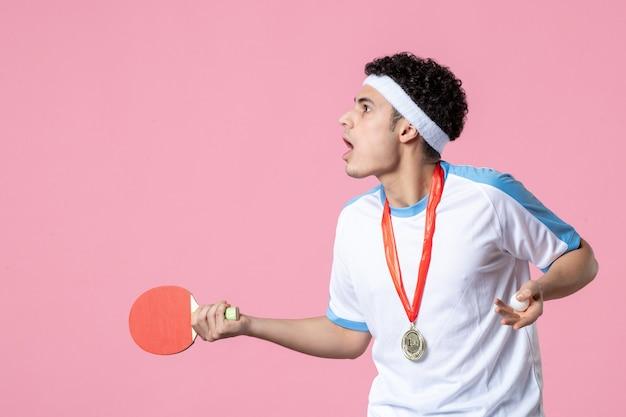 Vooraanzicht verwarde mannelijke speler met weinig racket en medaille