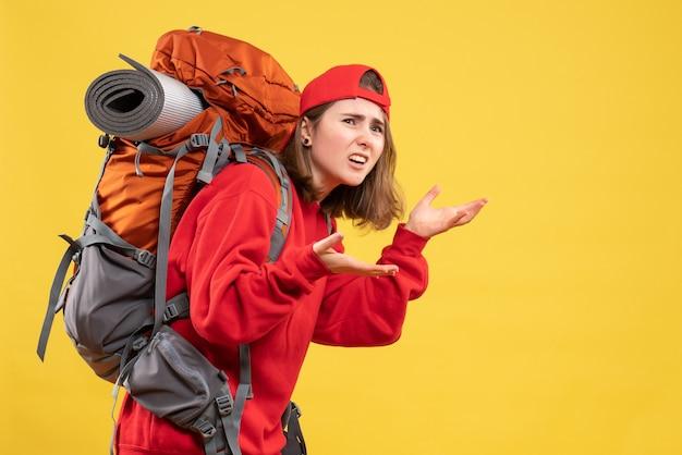 Vooraanzicht verwarde reizigersvrouw in rode rugzak