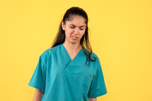 Vooraanzicht verwarde vrij vrouwelijke arts die zich op gele achtergrond bevindt