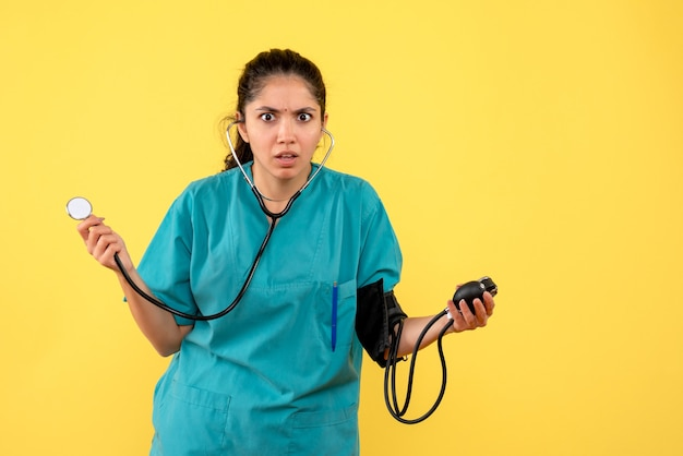 Vooraanzicht verwarde vrouwelijke arts in uniform met behulp van bloeddrukmeters staande op gele achtergrond