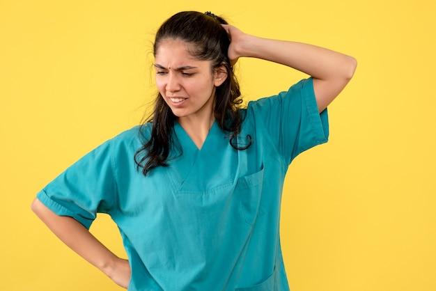 Vooraanzicht verwarde vrouwelijke arts in uniform staande op gele achtergrond