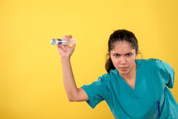 Vooraanzicht verwarde vrouwelijke arts met spuit op gele achtergrond