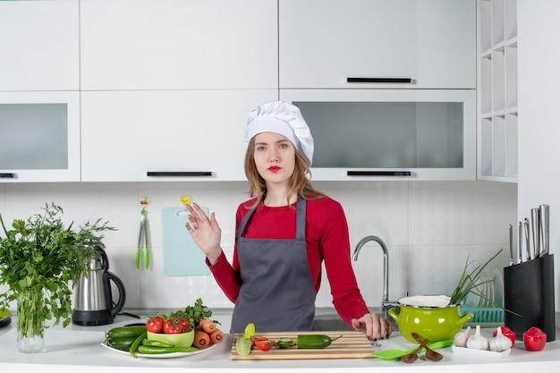 Vooraanzicht verwarde vrouwelijke chef-kok in schort die achter tafel staat