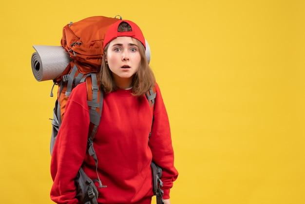Vooraanzicht verwarde vrouwelijke reiziger met rugzak die voorzijde bekijkt