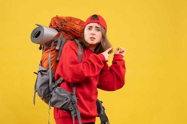 Vooraanzicht verwarde vrouwelijke reiziger met rugzak wijzende vingers erachter