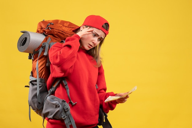 Vooraanzicht verwarde vrouwelijke toerist met de reiskaart van de rugzakholding