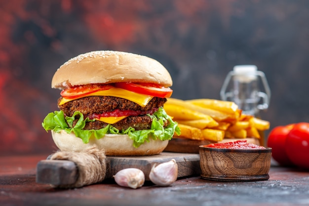 Vooraanzicht vlees hamburger met tomaten kaas en salade op donkere vloer broodje sandwich fastfood