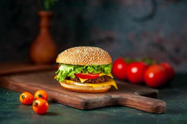 Vooraanzicht vlees hamburger met verse tomaten op donkere achtergrond