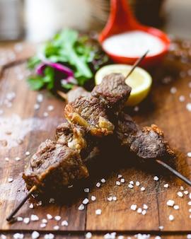 Vooraanzicht vlees kebab op spiesjes met zout en een schijfje citroen op het bord