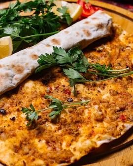 Vooraanzicht vlees lahmajun met peterselie en een schijfje citroen
