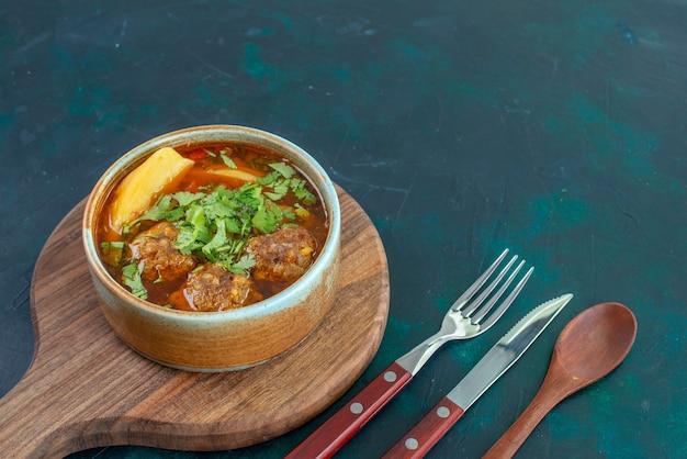 Vooraanzicht vleessoep met gehaktballetjes greens en gesneden aardappelen op de donkerblauwe van de de soepsaus van het bureauvoedsel de groenteschotel