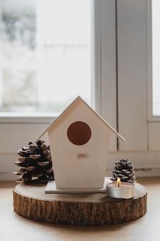 Vooraanzicht vogelhuisje met dennenappels en kaarsen