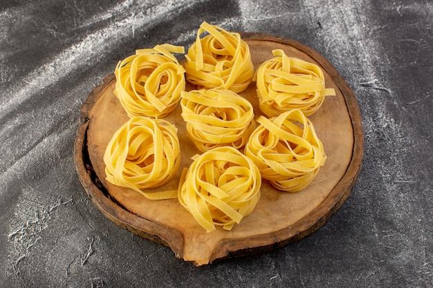 Vooraanzicht vormde italiaanse pasta in bloemvorm rauw en geel op bruin houten bureau