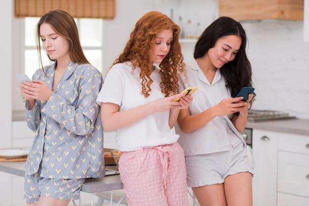 Vooraanzicht vriendinnen met behulp van telefoons