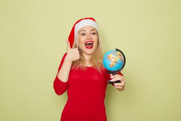 Vooraanzicht vrij vrouwelijk bedrijf kleine aardebol op groene muur vakantie emotie kerstmis nieuwjaar sneeuw kleuren