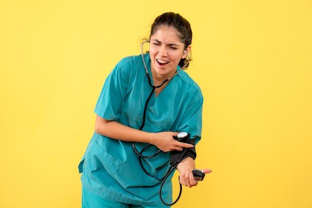 Vooraanzicht vrij vrouwelijke arts in uniforme bloeddrukmeters op gele achtergrond te houden