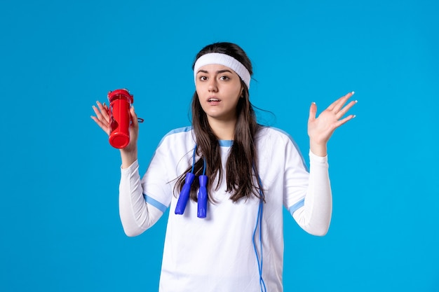 Vooraanzicht vrij wijfje in sportkleren met fles water op blauw
