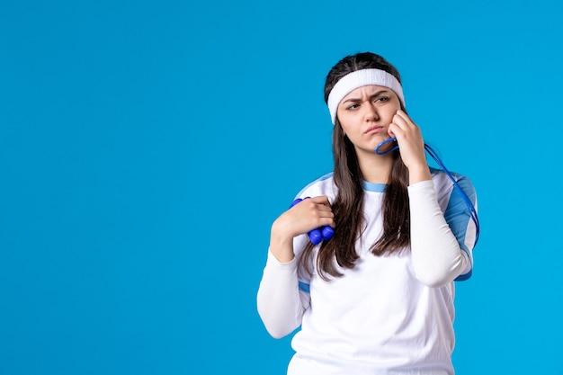 Vooraanzicht vrij wijfje in sportkleren met springtouw op blauw