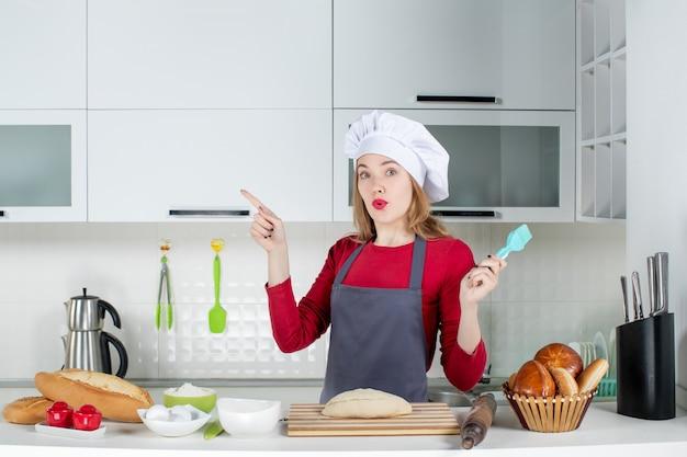 Vooraanzicht vroeg zich af blonde vrouw in koksmuts en schort wijzend naar links in de keuken