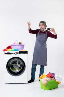 Vooraanzicht vroeg zich af hoe jonge man een kaart vasthoudt die in de buurt van een wasmachine op een witte muur staat