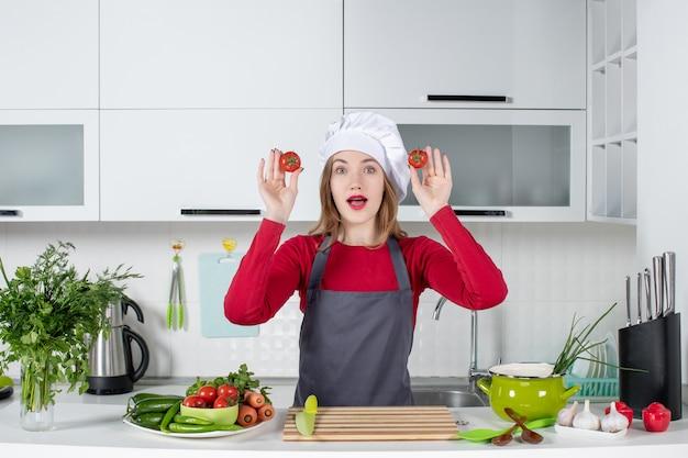 Vooraanzicht vroeg zich af hoe vrouwelijke kok in schort tomaten vasthoudt