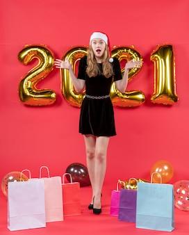 Vooraanzicht vroeg zich af jonge dame in zwarte jurk boodschappentassen op vloer ballonnen op rood