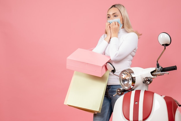 Vooraanzicht vroeg zich af jonge dame met boodschappentassen in de buurt van bromfiets