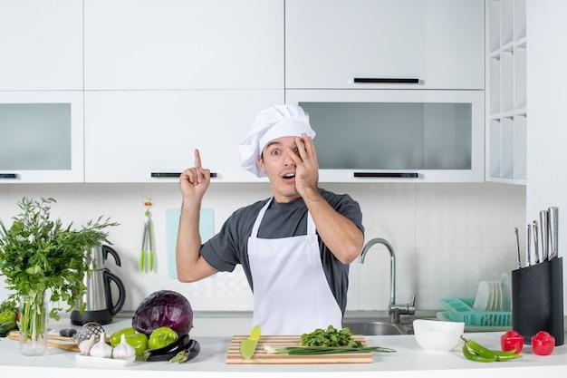 Vooraanzicht vroeg zich af jonge kok in uniform wijzend op keukenkast