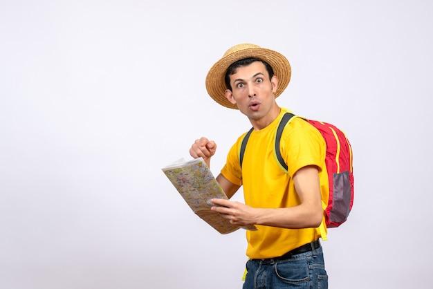 Vooraanzicht vroeg zich af jonge man met rode knapzak en geel t-shirt wijzend op de kaart