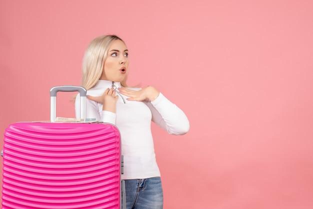 Vooraanzicht vroeg zich af mooie vrouw met roze koffer die naar iets keek