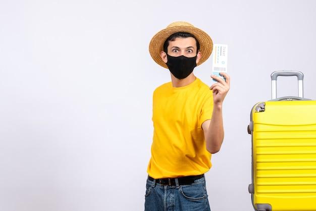Vooraanzicht vroeg zich af toerist in geel t-shirt die zich dichtbij gele koffer bevindt die reiskaartje steunt