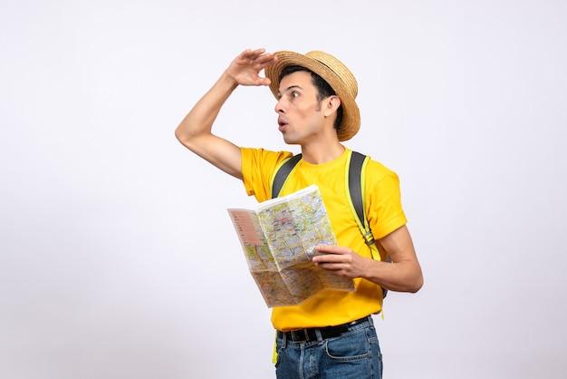 Vooraanzicht vroeg zich jonge man af die met strohoed en geel t-shirt kaart houdt die naar iets kijkt