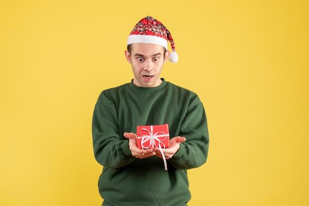 Vooraanzicht vroeg zich jonge man af die naar zijn geschenk op geel keek