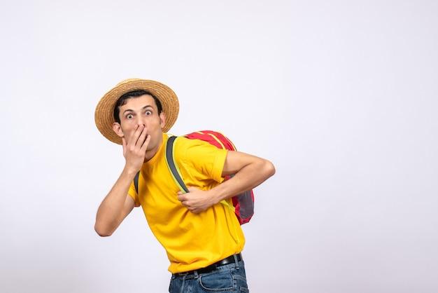 Vooraanzicht vroeg zich jonge man af met een strooien hoed en een geel t-shirt die hand voor zijn mond hield