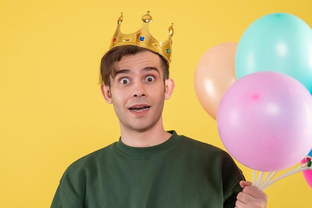 Vooraanzicht vroeg zich jonge man af met kroon die ballonnen op geel hield