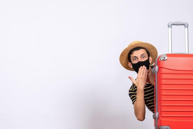 Vooraanzicht vroeg zich jonge toerist af met een zwart masker dat zich achter een rode koffer verstopte