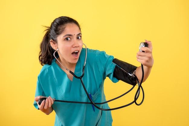 Vooraanzicht vroeg zich jonge vrouwelijke arts met bloeddrukmeter op gele achtergrond af
