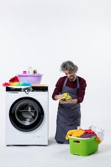 Vooraanzicht vrolijke huishoudster man staande op de knie met schoonmaakdoekje op witte achtergrond