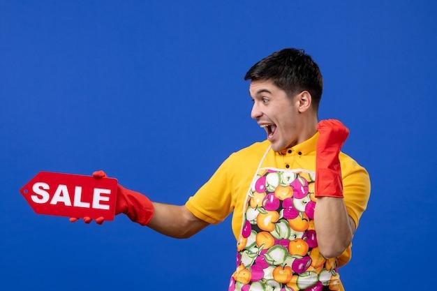 Vooraanzicht vrolijke jonge huishoudster met verkoopbord dat zijn geluk op blauwe ruimte toont