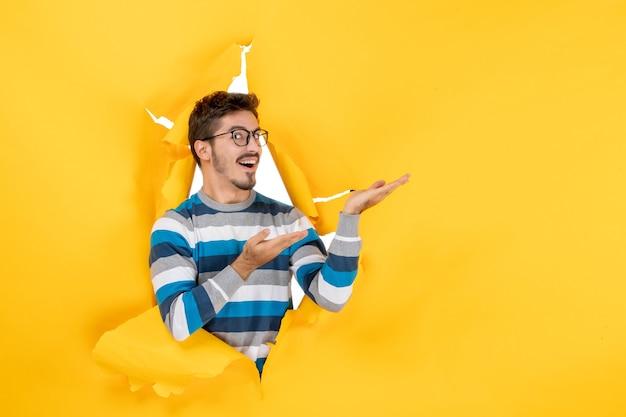 Vooraanzicht vrolijke jonge man gluren door gat in papier gele muur