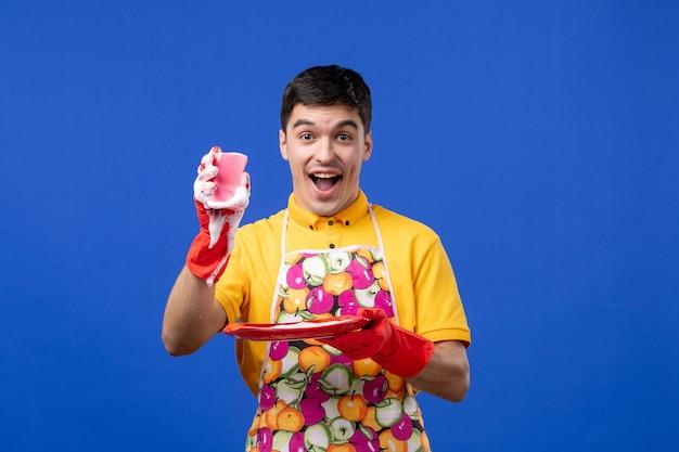 Vooraanzicht vrolijke mannelijke huishoudster die spons op blauwe ruimte toont