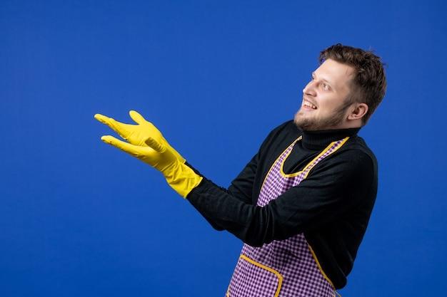 Vooraanzicht vrolijke mannelijke huishoudster wijzend op iets iets op blauwe geïsoleerde ruimte