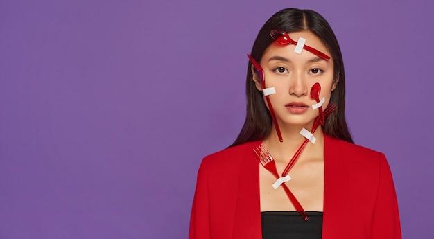 Vooraanzicht vrouw bedekt met rood plastic serviesgoed