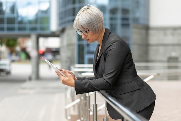 Vooraanzicht vrouw buiten kijken op tablet