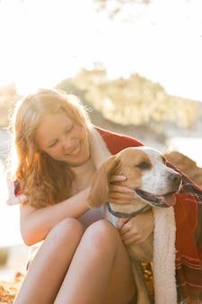 Vooraanzicht vrouw en hond gewikkeld in een deken
